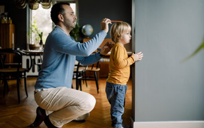 Full length of father measuring daughter's height against wall at home
