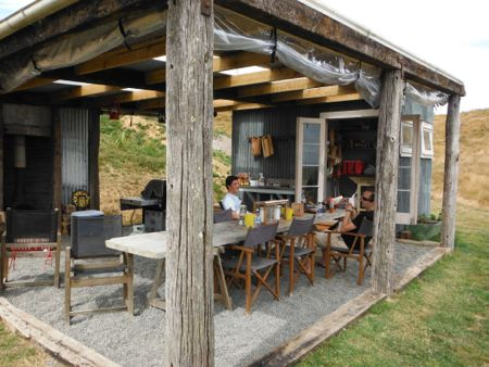 A covered outdoor kitchen area, with Nick and Kai sitting at a long table.