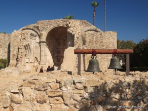 """A view of the ruins of Mission San Juan Capistrano's """"Great Stone Church,"""" destroyed by earthquake in 1812. These bells are located where the bell tower stood."""