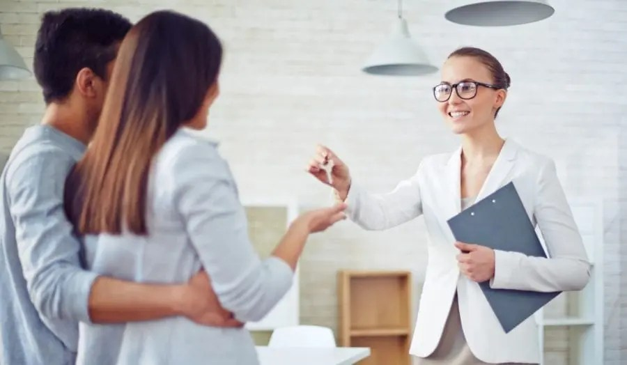 professional woman handing keys to a young couple