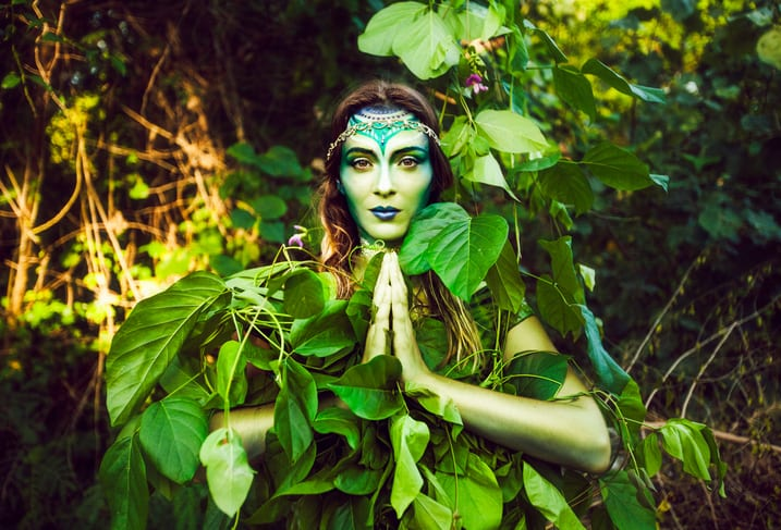 Beautiful woman with creative green makeup, blending in with the jungle.