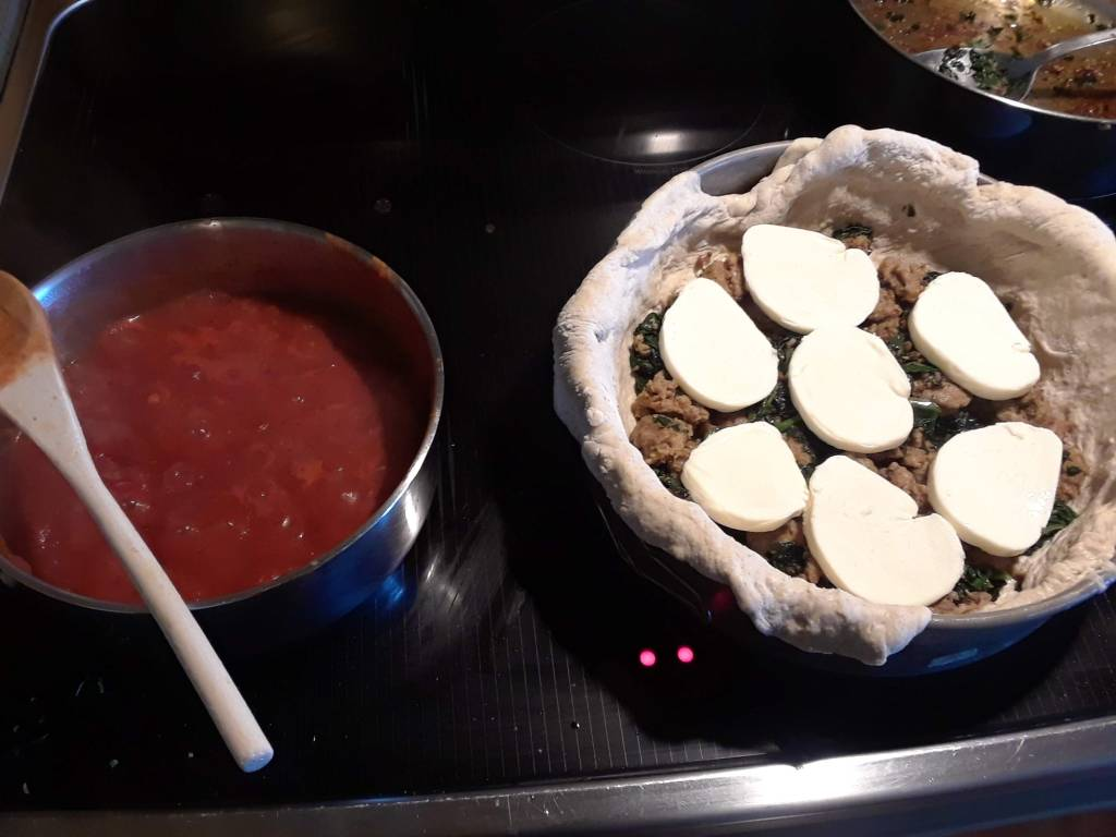 Chicago-style deep dish pizza, being assembled, and tomato sauce on a stove