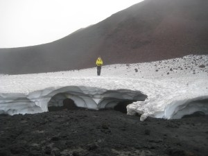 Our guide stands on a snowfield melting over the lava.