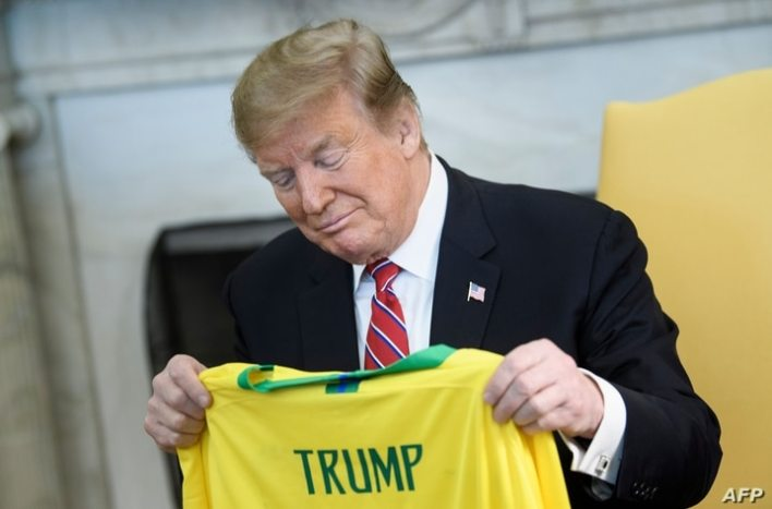(FILES) In this file picture taken on March 19, 2019 US President Donald Trump looks at a soccer jersey given by Brazil's…