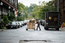 In this May 22, 2020, photo, a delivery man pushes a cart full of packages to deliver to an apartment building on an almost…