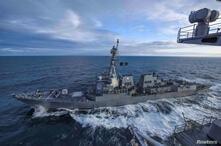 El destructor USS Kidd navega junto al portaaviones USS Theodore Roosevelt durante maniobras militares en el golfo de Alaska, el 16 de mayo de 2019. En estos momentos, ambas naves permanecen en puerto debido al nuevo coronavirus.