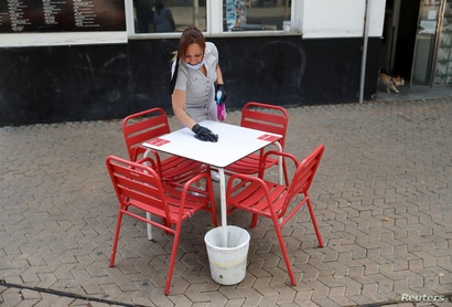 A woman cleans a table outside a bar, as some Spanish provinces are allowed to ease restrictions during the phase one amid the…