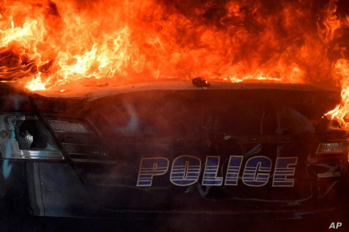 An Atlanta Police Department vehicle burns during a demonstration against police violence, Friday, May 29, 2020 in Atlanta. The…