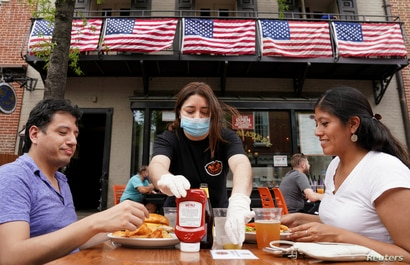 FILE PHOTO: As Phase One of reopening begins in Northern Virginia, a waitress with a face mask to protect against the…