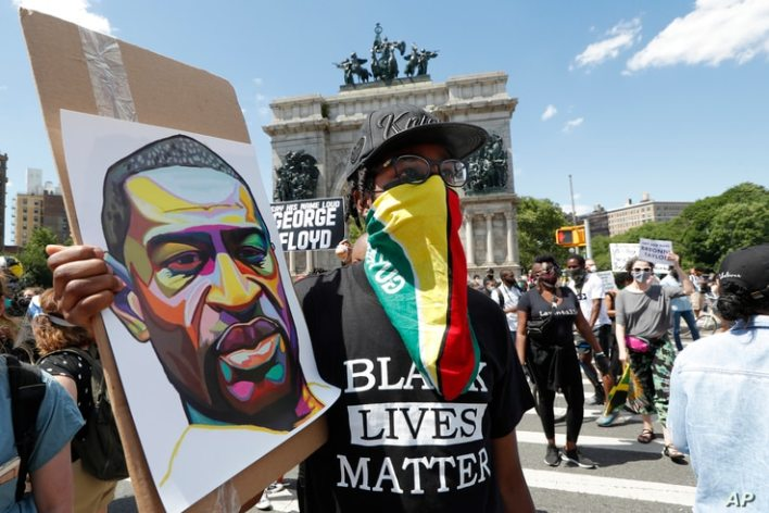 A man wears a Guyanese flag as his face protection as he listens to speakers during a Caribbean-led Black Lives Matter rally at…
