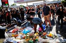 La gente se reúne alrededor de un monumento improvisado para conmemorar la muerte de George Floyd, el hombre afroamericano que falleció en Minnesota después de que un policía blanco presionara su rodilla contra su cuello