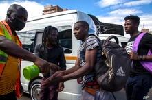 Jacob Maphala, un regulador de taxis con una máscara facial, rocía desinfectante a los pasajeros para protegerse contra el coronavirus, en una estación de taxis en Johannesburgo, Sudáfrica. Marzo 26 de 2020.