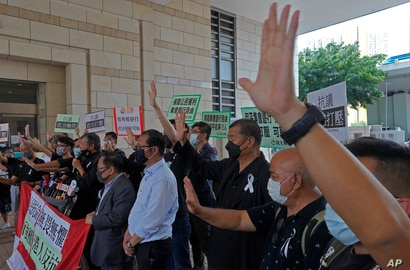Hong Kong media tycoon Jimmy Lai, third from right, shouts slogans with pro-democracy activists outside a court for charges…