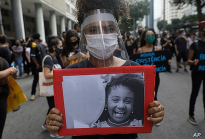 A woman wearing a face shield amid the new coronavirus pandemic holds a photo of Agatha, 8, a black child who was shot dead…