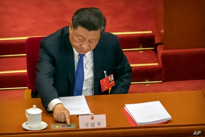 Chinese President Xi Jinping reaches to vote on a piece of national security legislation concerning Hong Kong during the…