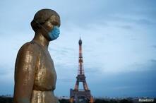 La estatua de oro en la plaza Trocadero, cerca de la torre Eiffel, usa una máscara protectora durante el brote de la enfermedad por coronavirus (COVID-19) en París, Francia.