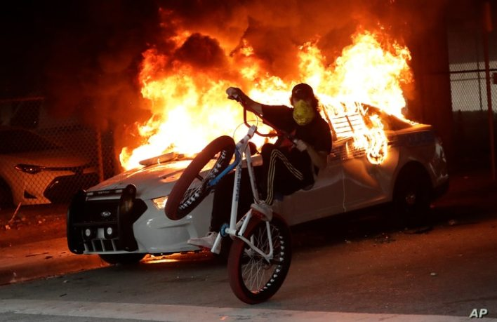A protester on a bicycle rides past a burning police car during a demonstration next to the city of Miami Police Department,…
