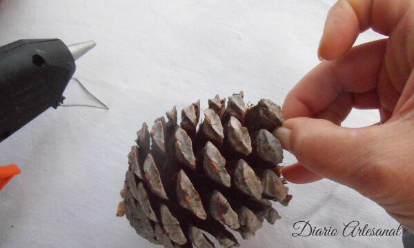 Pegando las escamas a la piña de pino