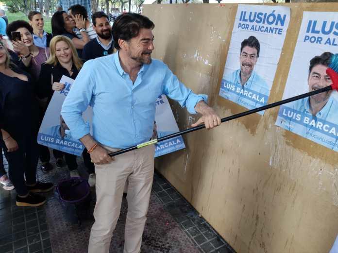 Barcala pegando el cartel de su campaña