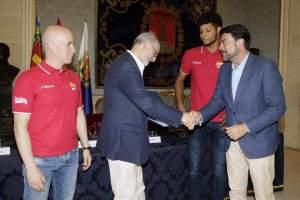Barcala dando la mano y entregando un obsequio a Arturo Ruiz ante la mirada del seleccionador y jugador nacional / Luis Barcala