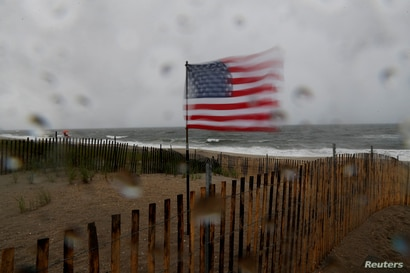A U.S. flag blows in heavy wind at the beach, as Tropical Storm Fay was expected to sweep across the heavily populated…