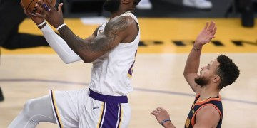 LeBron James, do Los Angeles Lakers, faz pontos sobre Stephen Curry, do Golden State Warriors, no Staples Center — Foto: Harry How/Getty Images