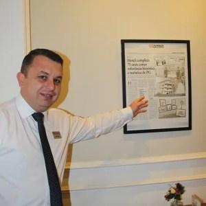 Anderson Machado, coordenador comercial do hotel mostra jornal que fala sobre passagem de Getúlio Vargas em Ponta Grossa