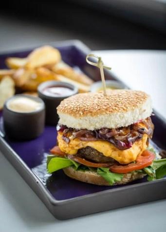 Novotel Burger é uma suculenta opção de hambúrguer de picanha com queijo meia cura derretido, cebola caramelizada e crispy de bacon no pão integral. Acompanha batata rústica, chips de mandioquinha ou de batata doce, além de molho aioli (Foto: divulgação)