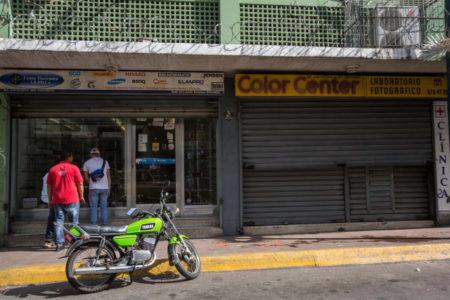Un local comercial abierto y otro cerrado hoy, viernes 28 de octubre de 2016, en Caracas (Venezuela). El paro general de 12 horas convocado por la oposición venezolana se cumple a medias en el país pues tanto las entidades bancarias como algunos comercios y oficinas abrieron sus puertas, sin embargo, las principales vías se mostraron con mucho menos tráfico que el que se observa en un día laboral normal. EFE/MIGUEL GUTIÈRREZ