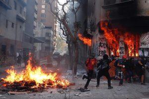 """AME2572. SANTIAGO (CHILE), 14/02/2020.- Manifestantes y Carabineros se enfrentan este viernes en inmediaciones a la Plaza Italia, rebautizada como """"Plaza de la Dignidad"""", durante una nueva jornada de movilizaciones en Santiago (Chile). Miles de personas acudieron este viernes a Plaza Italia, epicentro de las protestas en Chile, para celebrar el Día de los Enamorados y pedir la salida del cuestionado jefe de la Policía, Mario Rozas, tras las reiteradas denuncias contra el cuerpo de seguridad por violación a los derechos humanos. EFE/Alberto Valdés"""