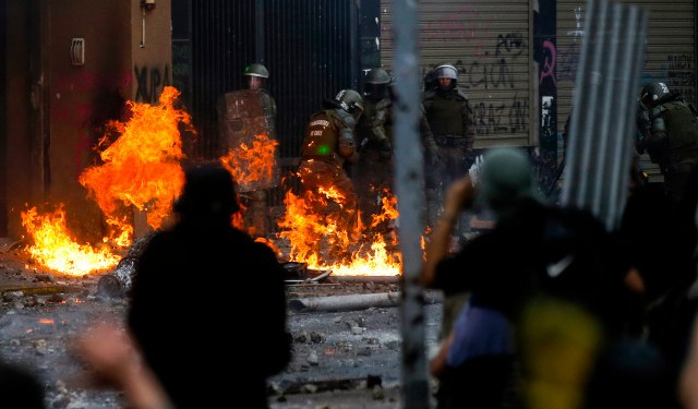 Riot police are reached by a petrol bomb during clashes with demonstrators protesting, in Santiago, on November 8, 2019. - Unrest began in Chile last October 18 with protests against a rise in transport tickets and other austerity measures that descended into vandalism, looting, and clashes between demonstrators and police. (Photo by JAVIER TORRES / AFP)
