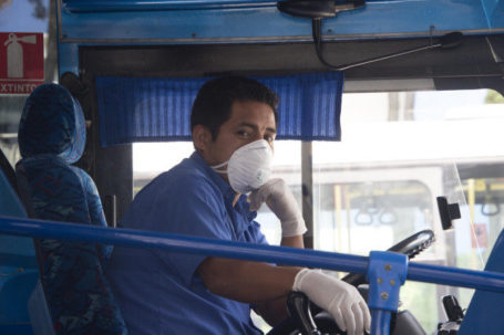 A bus driver wears a protective mask as a preventive measure against the spread of the COVID-19 Coronavirus, at a transfer station in Quito, on March 13, 2020. (Photo by Rodrigo BUENDIA / AFP)