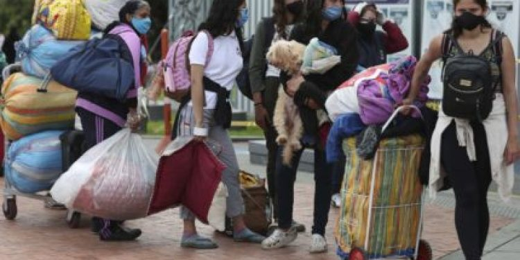 Venezuelan migrants wait for a bus to travel to the border, after breaking camp in Bogota, Colombia, Thursday, July 2, 2020. Facing no work due to the COVID-19-related economic shutdown, hundreds of Venezuelan migrants are returning to their country. (AP Photo/Fernando Vergara)