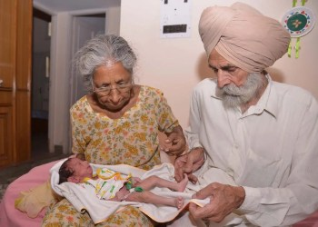 Indian parents Mohinder Singh Gill (L), 79, and Daljinder Kaur, 70, hold their newborn baby boy Arman at their home in Amritsar on May 11, 2016. An Indian woman who gave birth at the age of 70 said May 10 she was not too old to become a first-time mother, adding that her life was now complete. Daljinder Kaur gave birth last month to a boy following two years of IVF treatment at a fertility clinic in the northern state of Haryana with her 79-year-old husband.  / AFP / NARINDER NANU