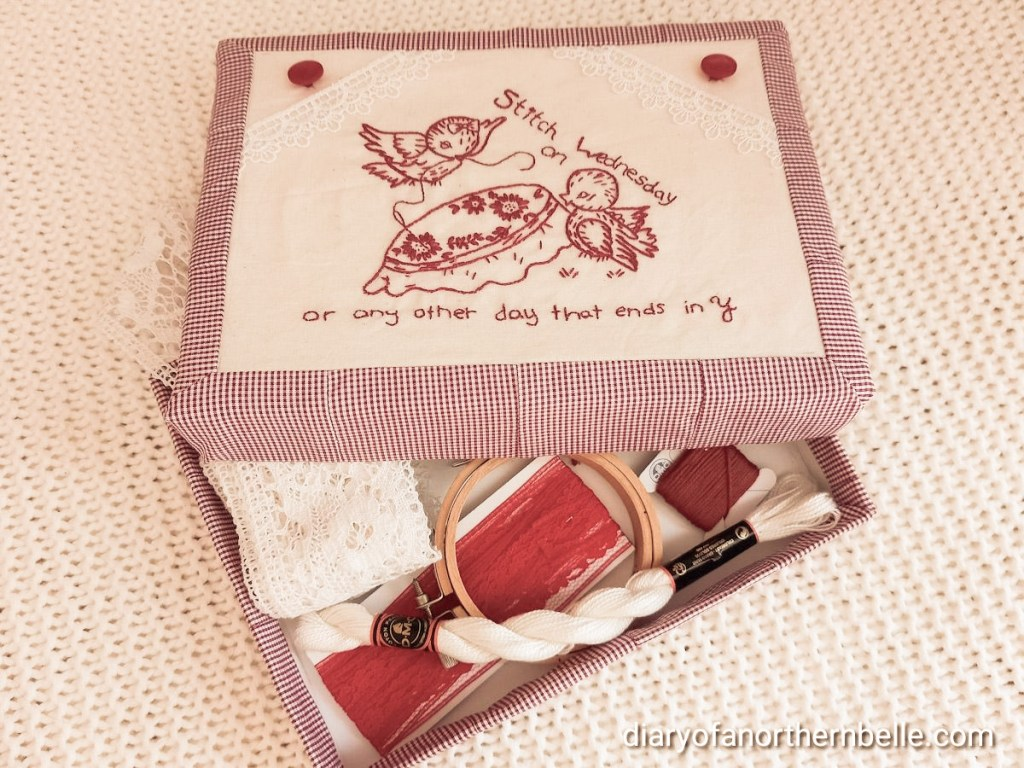 finished project filled with various sewing supplies like lace, thread, embroidery hoop, floss