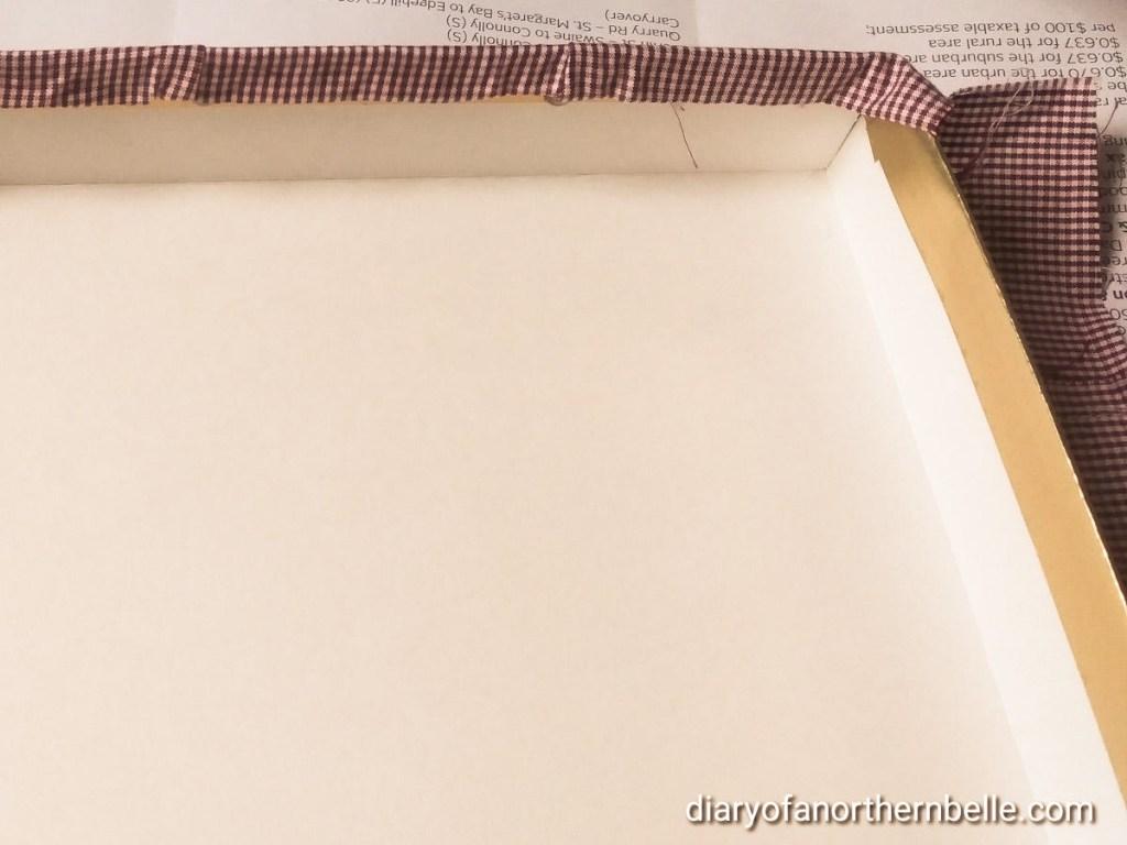 gingham fabric being hot glued around box