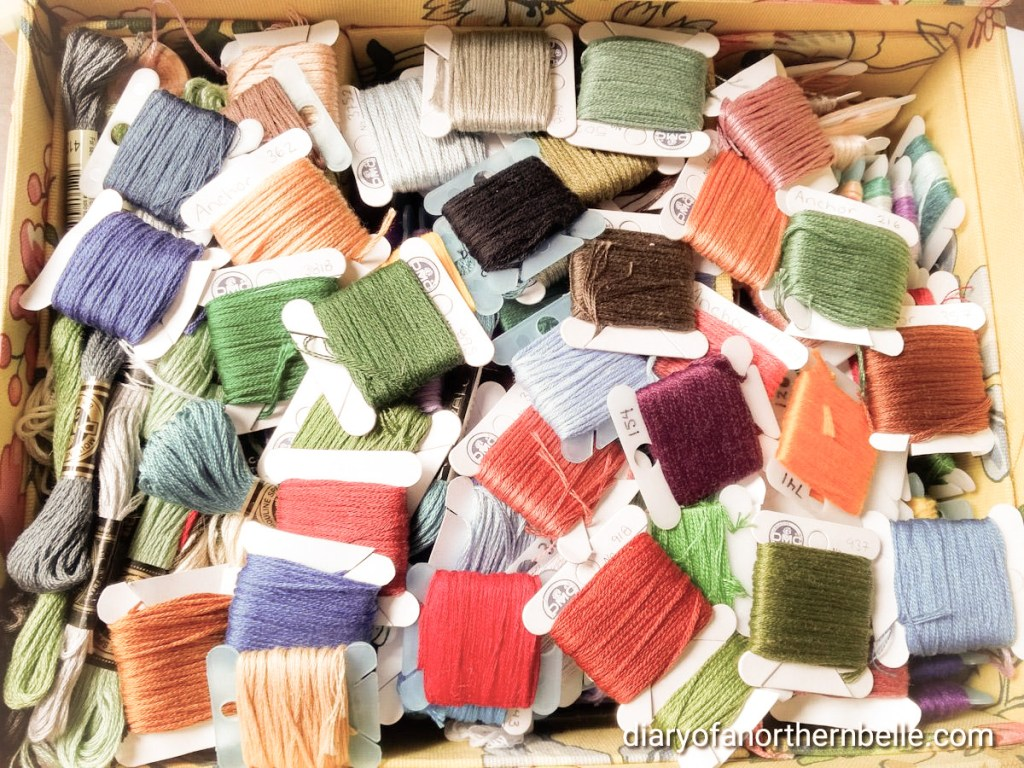 A box full of miscellaneous DMC and Anchor embroidery thread, winded on cardboard cards