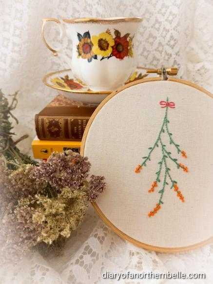 embroidery hoop art featuring hanging branch stitched in green with orange buds