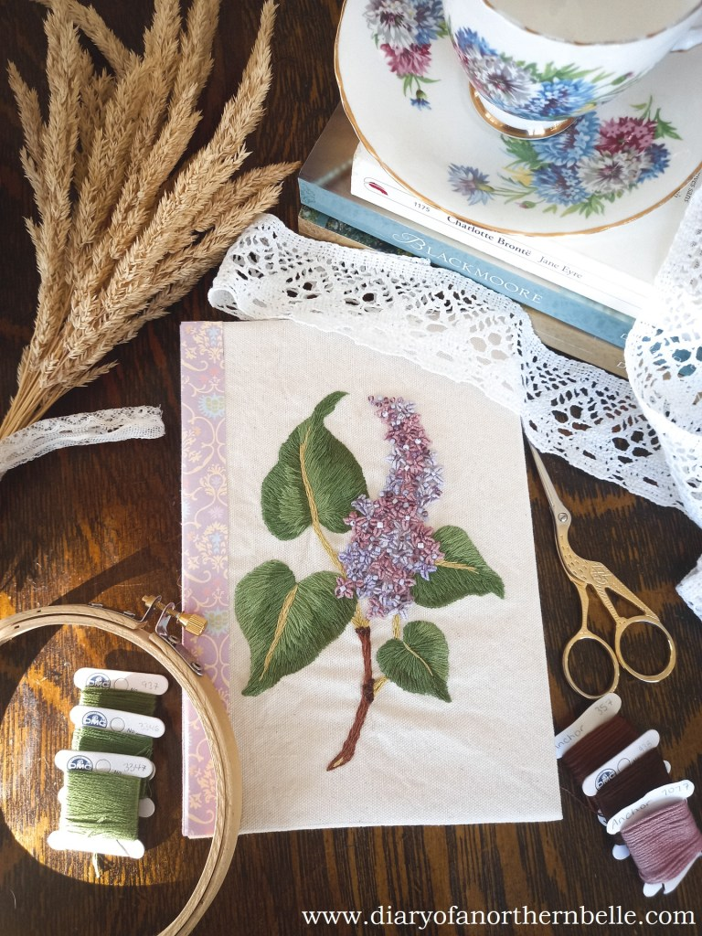 flat lay view of embroidered lilac branch journal cover
