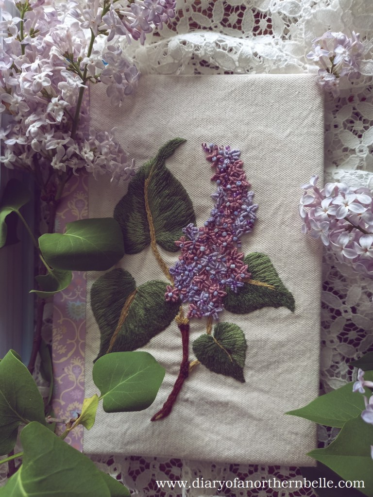 view of finished embroidery surrounded by fresh lilac