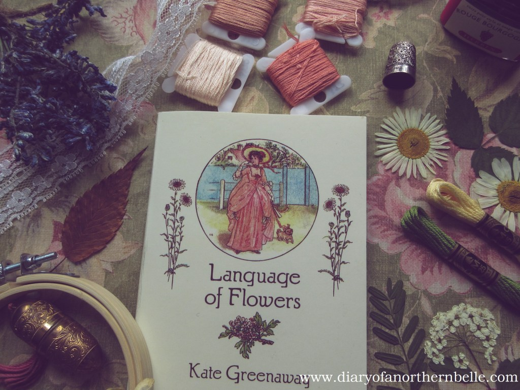 flat lay view of Language of Flowers dictionary, embroidery floss, dried flowers