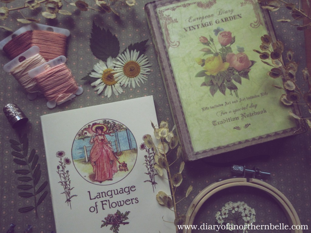 floriography dictionary and vintage garden diary surrounded by dried flowers