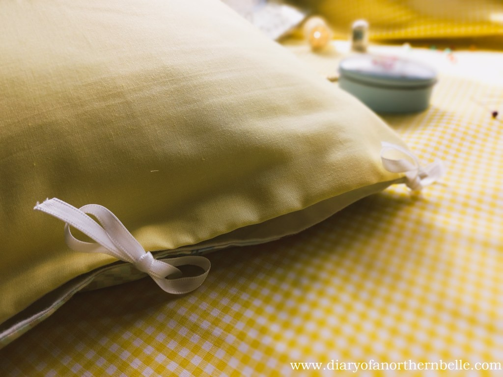 close up of embroidered pillow case opening with ribbons