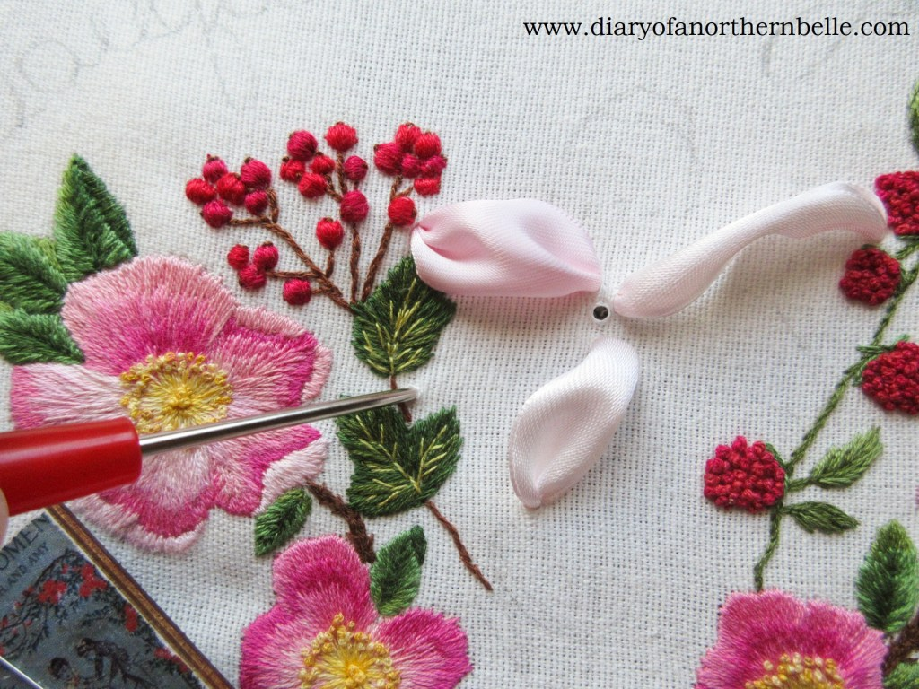 using an awl to poke holes through the fabric for the ribbon lily