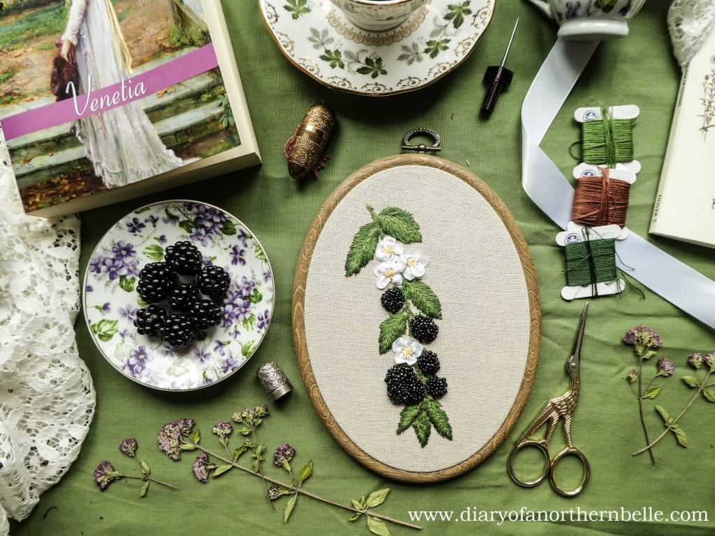 flat lay close-up on beaded blackberries project and plate of blackberries with embroidery notions and dried flowers