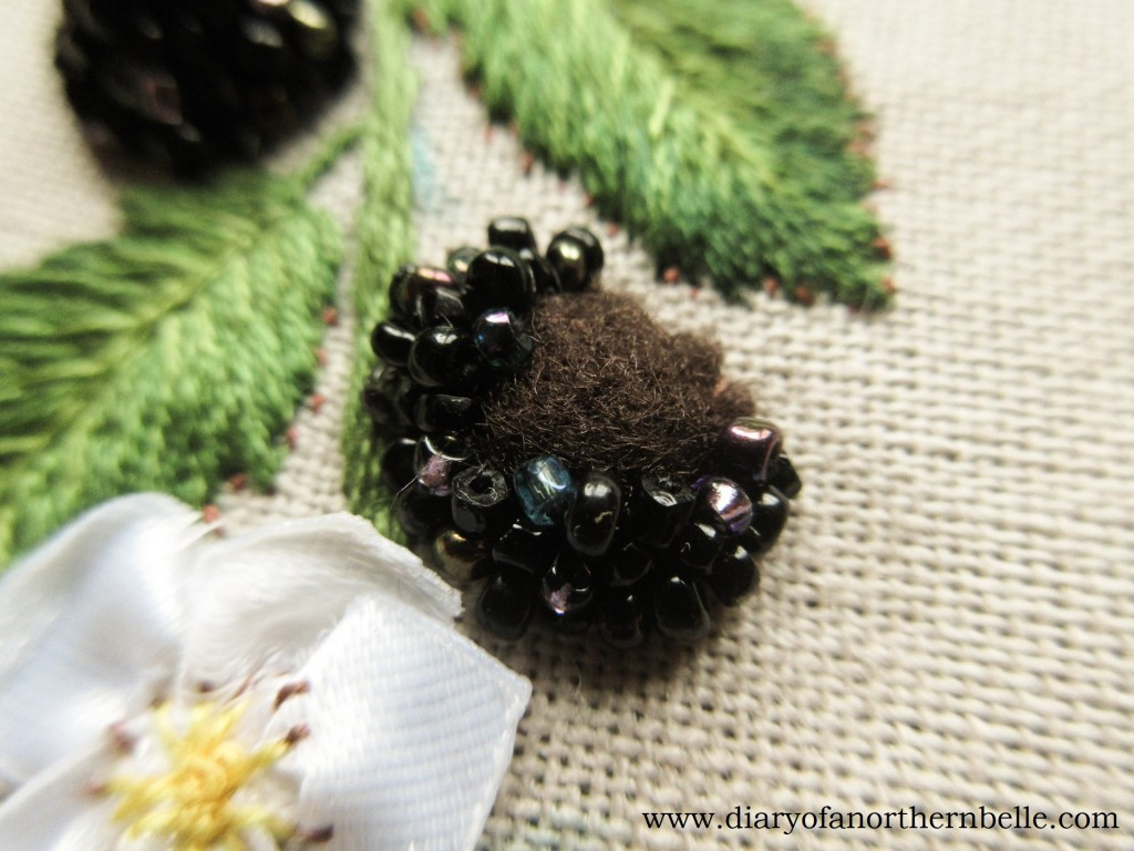 close-up of beaded blackberry in the making; beads are stitch on a padded piece of felt