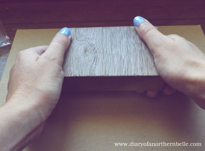 hands pushing a wooden block on the plastic pusher to secure button back