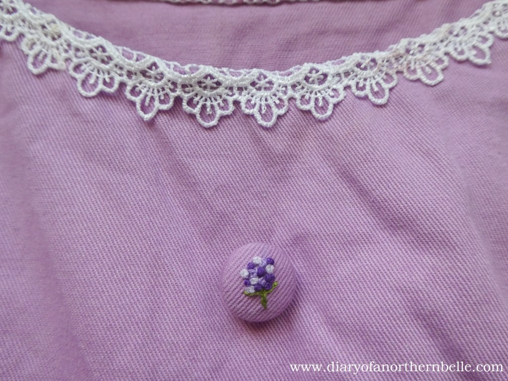 close-up of top embroidered button on lilac dress bodice front