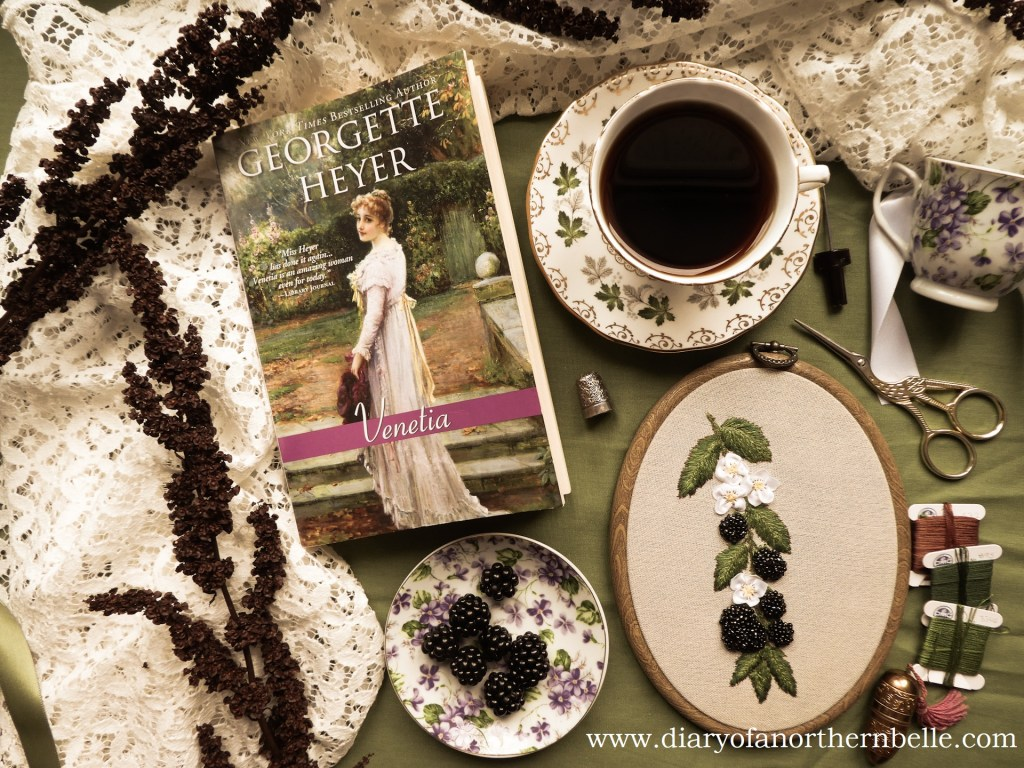 flat lay view of Venetia book, plate of blackberries, beaded blackberries project, cup of tea and embroidery notions