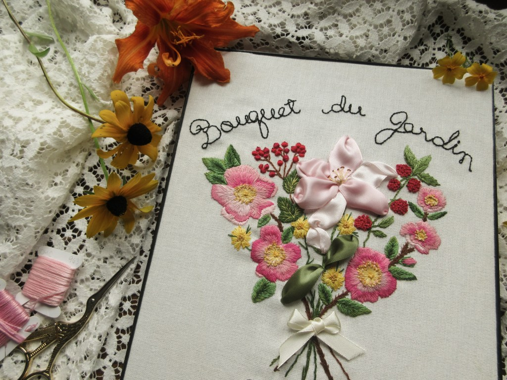 view of the finished garden bouquet embroidery, framed and surrounded by flowers